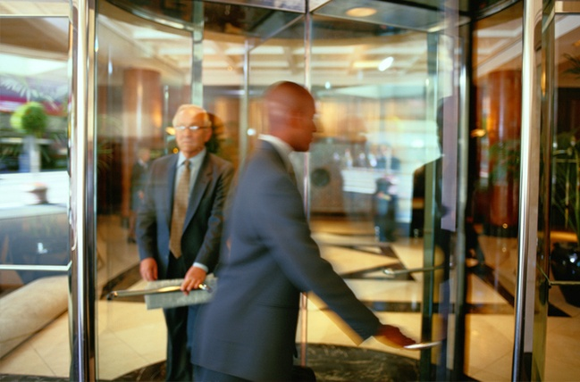 Two business men walking through a revolving door